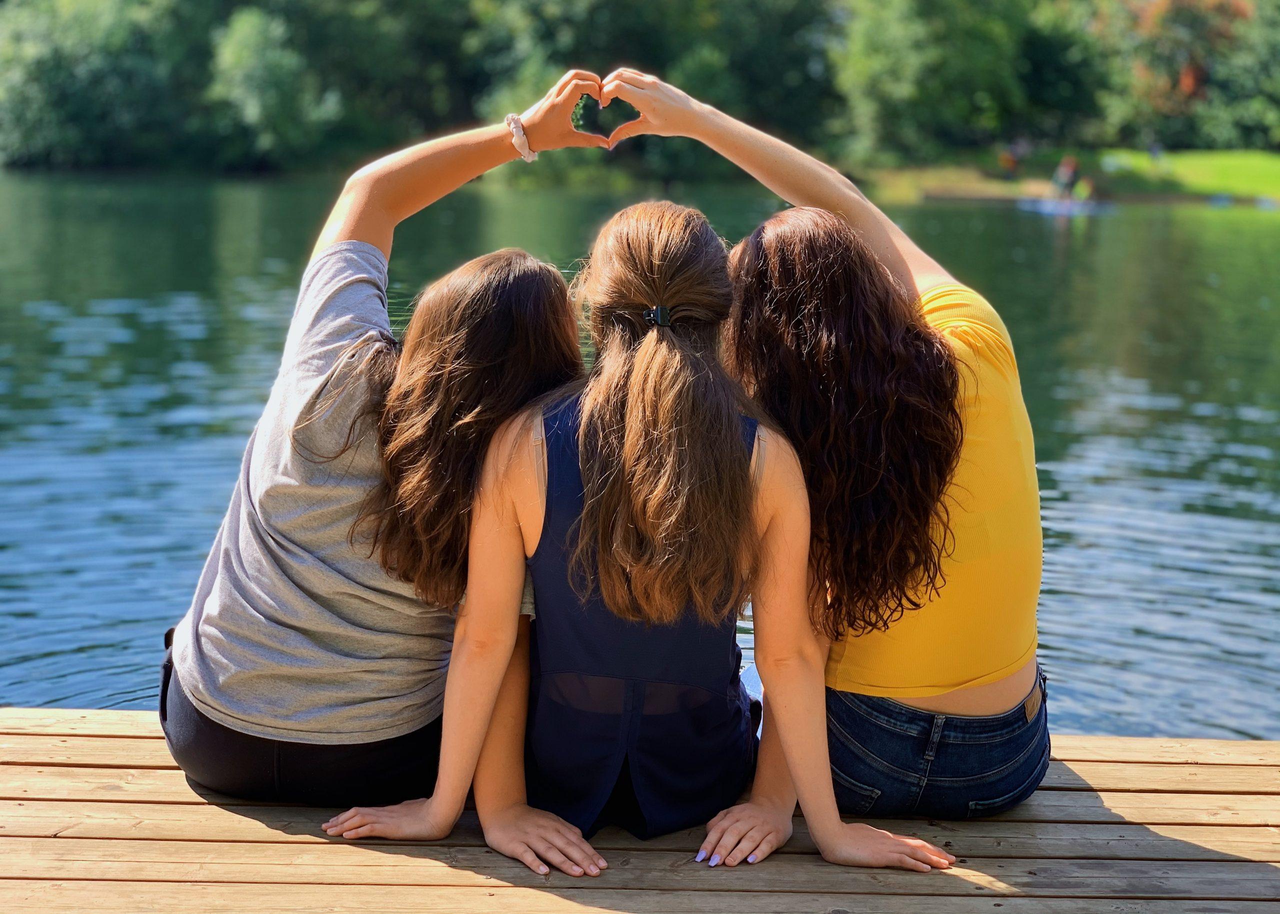 2 women sitting on wooden dock during daytime